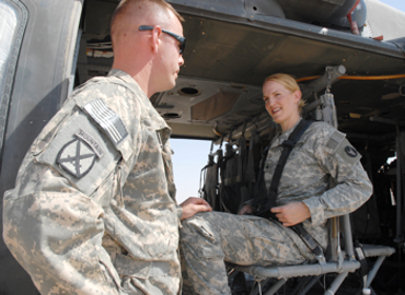 Army Chief Warrant Officer 3 Heath Wieseler catches up on old times with his sister, Army Sgt. Andrea Wieseler, in a UH-60 Black Hawk helicopter on Contingency Operating Base Speicher, Iraq, Aug. 13, 2009. The siblings spent a few days together after not seeing each other for more than two years.