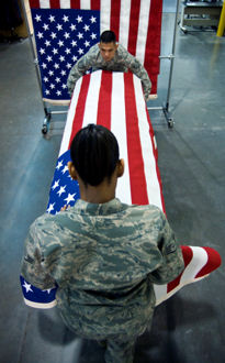 Air Force Staff Sgt. Star Samuels, front, and Air Force Tech. Sgt. Willard Rico place a U.S. flag over a casket March 31, 2009, during a dry run of shipping process procedures for the dignified transfer of remains at the Charles C. Carson Center for Mortuary Affairs, Dover Air Force Base, Del.