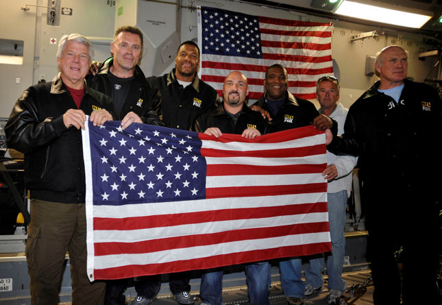 "The ""Fox NFL Sunday"" team holds up a flag onboard a C-17 Globemaster III that was presented to them by Lt. Col Richard Williamson Nov. 5, 2009, on an airdrop mission over Afghanistan. The NFL team participated in an airdrop that supported ground troops in Afghanistan. Colonel Williamson is the 816th Expeditionary Airlift Squadron commander deployed to Southwest Asia."