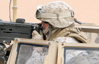 Marine Corps Cpl. Susy H. Aguilar sights in and prepares her .50-caliber machine gun for a test fire at Al Asad Air Base, Iraq, April 21, 2009. Aguilar extended her contract with the Marine Corps to deploy as a machine gunner. She serves with Transportation Support Company, Combat Logistics Battalion 7, 2nd Marine Logistics Group