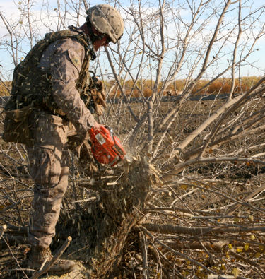 Marine Corps Cpl. Jonathan Lehman, a combat engineer, cuts down a tree to make room for the construction of an observation post in Helmand province, Afghanistan, Dec. 18, 2009.