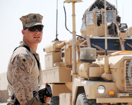 Marine Corps Sgt. Justin D. Toren waits for the departure of a convoy to Habbaniyah Tourist Village, Iraq, Aug. 11, 2009.