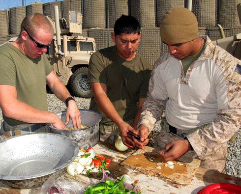 Navy Seaman Timothy Wienke and Marine Corps Cpls. Carlos Martinez and Carlos J. Orellana chop vegetables, season meat and cook sides at the Patrol Base Jaker custom field kitchen in Afghanistan's Helmand province, Dec. 5, 2009.