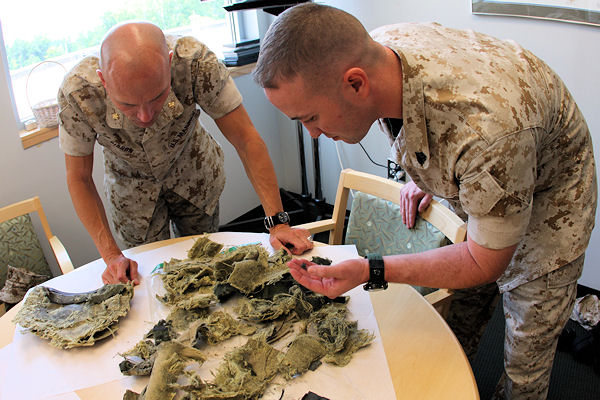 National Museum Of The Marine Corps, Quantico, VA.- For the first time in more than five years, Sgt. Mark Dean, one of Medal of Honor recipient Cpl. Jason Dunham's close friends, and Maj. Trent A. Gibson, Dunham's former company commander, carefully sort out the pieces of the Kevlar helmet Dunham used to help absorb the blast of a grenade in the streets of Iraq in 2004. The pair delivered the helmet to the National Museum of the Marine Corps July 9, 2009 to be displayed in the coming years.