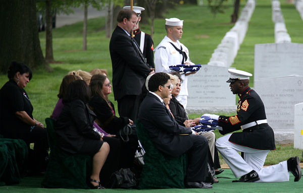ARLINGTON, Va.-Sgt Maj. Ronald Green presents burial flags to family members of six Vietnam War casualties during a repatriation service May 14, 2009. After 41 years, the remains of six Marines killed in Vietnam were identified, repatriated and interred in a group burial.