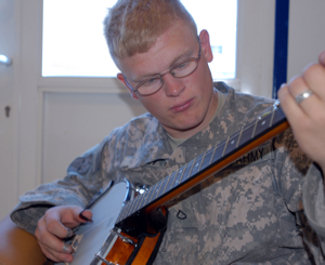 Pfc. Christian J. Josey, an infantryman for Headquarters and Headquarters Company, 172nd Infantry Brigade plays banjo at the Greenbeen Coffee lounge here. Josey has played banjo for 10 years and has placed in two different fiddler conventions.