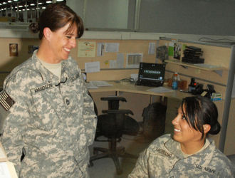 Army Sgt. 1st Class Angela Amundson, left, discusses correct wording for awards with one of her soldiers at Contingency Operating Base Basra, Iraq, May 6, 2009. The mother of two will spend Mother's Day helping other deployed mothers observe the day.