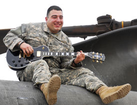 Army Sgt. Nicholas Raia strums his guitar on top of a CH-47 Chinook helicopter at Contingency Operating Base Adder, Iraq, Oct., 24, 2009. Raia, who performs in the Pennsylvania National Guard's 28th Infantry Division Band, volunteered to deploy as a door gunner with the 28th Combat Aviation Brigade.