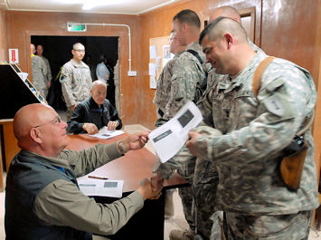 Medal of Honor recipients retired Army Command Sgt. Maj. Gary Littrell, left, and retired Army Col. Robert Howard, center, sign and hand out copies of their award citations to soldiers serving in Multinational Division Baghdad with the 1st Infantry Division's 2nd Heavy Brigade Combat Team on Camp Liberty, Iraq, April 14, 2009.