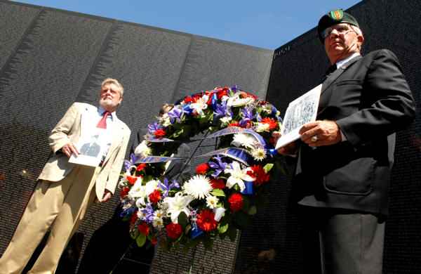 Retired U.S. Army Capt. Nathaniel P. Ward IV, left, and retired Army Maj. Sam Ratcliffe stand in front of the Vietnam War Memorial Wall July 8, 2009, in Washington, D.C., after laying a wreath in honor of the 50th Anniversary of the first two American servicemembers to be killed in the Vietnam War. Ward and Ratcliffe are also holding photographs of the two soldiers: Army Master Sgt. Chester Ovnand and Maj. Dale Buis. They were killed when their compound in Bien Hoa, just north of Saigon, was attacked.