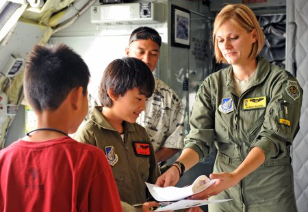Capt. Jasmine McCann gives 11-year-old Ryder Lum and his best friend Everett Fan mementos from their tour of a KC-135 Stratotanker Oct. 29, 2010, at Joint Base Pearl Harbor-Hickam, Hawaii. Ryder was part of the 535th Airlift Squadron's quarterly Pilot for a Day program, which allows children with catastrophic disorders or illnesses to experience a day in the life of an Air Force pilot.