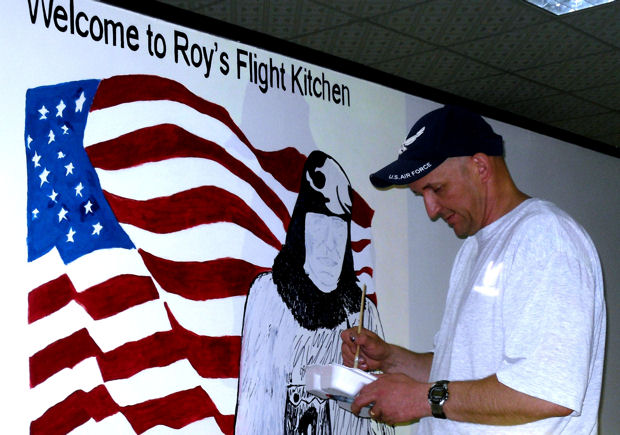 Master Sgt. Scott Sturkol works on a mural honoring Master Sgt. Roy Hooe April 18, 2010 inside Roy's Flight Kitchen at an air base in Southwest Asia. Sergeant Sturkol is the superintendent of the 380th Air Expeditionary Wing Public Affairs deployed from the Headquarters Air Mobility Command Public Affairs at Scott Air Force Base, Ill.