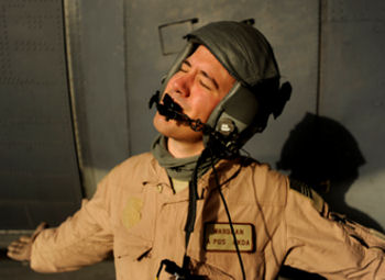Senior Airman J.C. Wardean, an HC-130P Hercules loadmaster assigned to the 79th Expeditionary Rescue Squadron, in a moment of levity, waits for a fuel truck to refuel an HC-130P aircraft, April 17, 2010, Kandahar Airfield, Afghanistan.