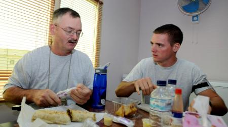 Senior Master Sgt. Robert Gunther and Airman 1st Class Robert Gunther Jr., a father and son deployed here from the Illinois Air National Guard, enjoy a meal together at an undisclosed air base Oct. 24, 2010. Sergeant Gunther, first sergeant for the 386th Expeditionary Civil Engineer Squadron, and Airman Gunther, an electrician in the same unit, often spend off-duty time together when not working. Photo by Senior Airman Laura Turner