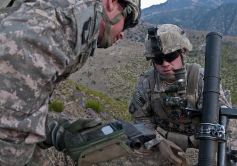 Army Spcs. Corey C. Canterbury, right, and Joshua R. Wood check their mortar tube and coordinates before firing mortar rounds on a mountainside overlooking the Ganjgal Valley, Afghanistan, Dec. 10, 2010. U.S. Army photo by Staff Sgt. Mark Burrell