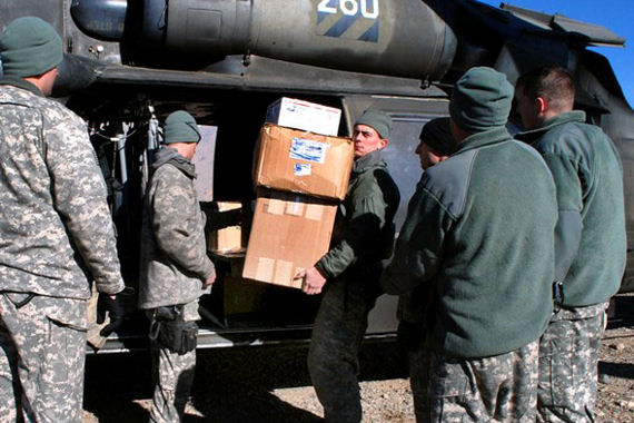 Army Sgt. Matthew West removes boxes of supplies from the back of a Black Hawk helicopter to be delivered to schools in and around Bamyan province in Afghanistan, Jan. 13, 2010.