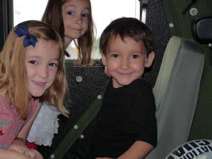 Jacob Beckmeyer and his sisters, Sarah and Grace, play in a National Guard Humvee prior to taking a ride.