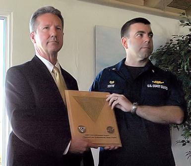Patrick Ward, left, acting deputy director for supply reduction and United States interdiction coordinator, presents Cmdr. Jon Totte, commanding officer, pacific tactical law enforcement team, with the 2009 United States Interdiction Coordinator Award to the Coast Guard PACTACLET at the Bay View Restaurant, here, Aug. 19. The award was established to recognize superior performance of front-line narcotics interdictors in the ongoing battle against drug smugglers and the organizations that support them.