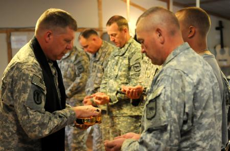 Lt. Col. David Gunderson, KBC command chaplain, 196th Maneuver Enhancement Brigade, South Dakota Army National Guard, hands out communion during the Lutheran service Sunday, Oct. 10, 2010 at Camp Phoenix Kabul, Afghanistan.