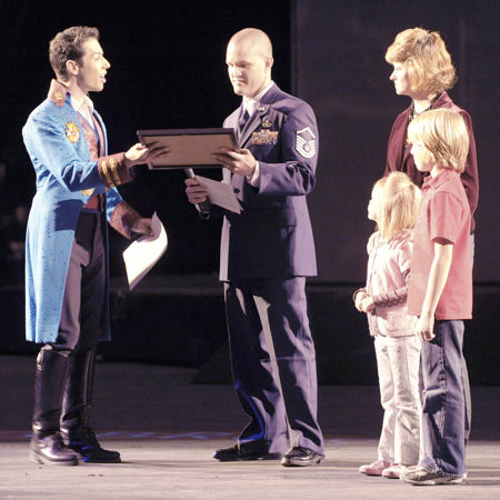 "Master Sgt. Cameron Rogers, along with his wife Maggie and children Sam and Laine, receive a certificate from Magical Zingmaster Alex Ramon designating the Rogers family as guest ringmasters for the Ringling Bros. and Barnum & Bailey ""Zing Zang Zoom"" circus performance March 26, 2010, at George Mason University's Patriot Center in Fairfax, Va. Sergeant Rogers is the Air Force District of Washington's UH-1N helicopter program manager at Bolling Air Force Base, D.C."