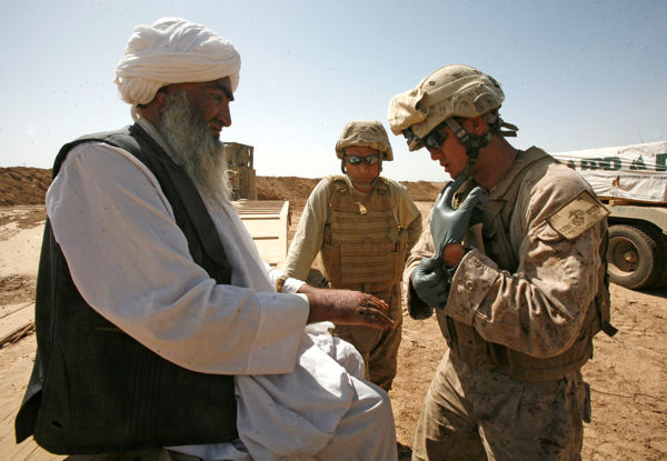 Navy Seaman Vince Edward Chu Lo, a corpsman with 2nd Combat Engineer Battalion, gives medical treatment to a resident of Marja, Afghanistan, March 7, 2010.