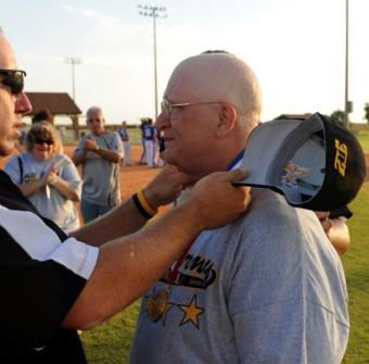 September 2010 - All-Army women's softball coach Sgt. 1st Class Rob Bailey of Fort Leonard Wood, Mo., hangs his gold medal around the neck of Debra Rogers, mother of All-Army second baseman Dann Rogers of Camp Walker, Korea, at the 2010 Armed Forces Softball Championships at Naval Air Station Pensacola, Fla. Despite battling breast cancer, Debra made the trip from Marinette, Wis., and attended all 17 of the All-Army men's and women's games.