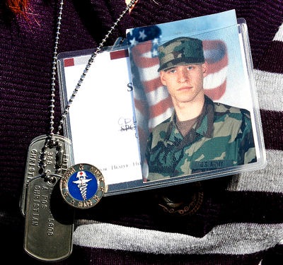 Sarah Fargo honors her brother's memory by wearing his photo and dog tags at a ceremony honoring fallen military medical personnel at Arlington National Cemetery in Arlington, Va., March 16, 2010. Army Cpl. Adam J. Fargo, a medic, was killed in Iraq in July 2006.