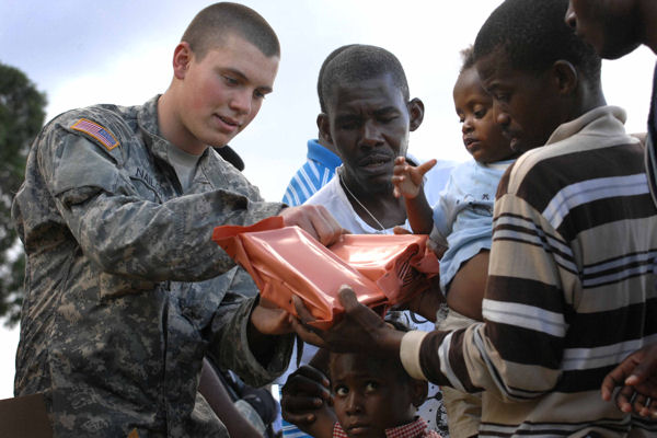Army Spc. Brent Nailor of the 82nd Airborne Division's 1st Squadron, 73rd Cavalry Regiment, passes out packaged meals to women and children in Port-au-Prince, Haiti, Jan. 16, 2010. The squadron established a forward operating base at an abandoned and damaged country club near the U.S. embassy. A survivor camp of thousands is situated near the base.