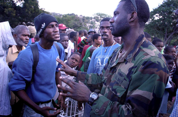 Navy Petty Officer 2nd Class Sandy Diogene, with the Maritime Civil Affairs unit out of Little Creek, Va., talks with Haitians waiting for food and water at a forward operating base in Port-au-Prince, Haiti, Jan. 16, 2010. Diogene was born in Haiti.