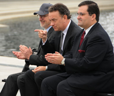 Actor Tom Hanks, center, points to 250 veterans at the World War II Memorial March 11, during a speech by HBO co-president Richard Plepler (not pictured). Producer / director Steven Spielberg is seated to the left of Tom Hanks.
