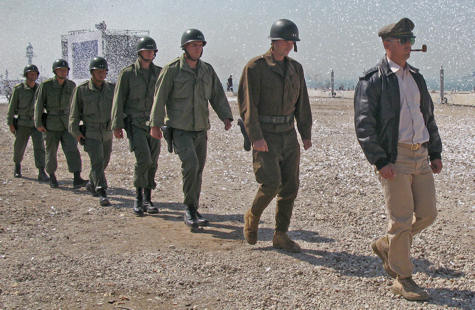 Army Gen. Douglas MacArthur, depicted by Marine Capt. Michael Borneo, right, marches across the beach amid a flurry of confetti, with fellow Marines depicting his key officers in tow during reenactment ceremonies of the Inchon Landing in the Republic of Korea, Sept. 15, 2010.