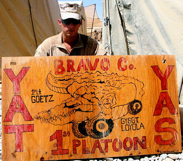 "Cpl. John A. Galvan, an assistant squad leader with Mine-Resistant, Ambush-Protected Company, 3rd Amphibious Assault Battalion, takes a knee by his unit logo poster he drew for his tents, as a show of unit pride when they first got to Marjah. ""Col. Newman saw it, he liked it and he asked me if I could paint the Afghan Flag as a favor to the governor,"" said Galvan. Galvan cut the garrison-sized flag out of plywood, and his tools were a sponge, Q-tips and his fingers"
