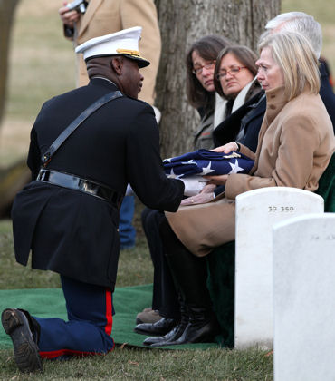 Col. Carlyle Shelton, serving as the representative of the office of the Commandant of the Marine Corps, presents a folded American flag to Jacqueline Mackin-Hartman, the daughter of retired Col. Alvin Mackin, at Arlington National Cemetery in Arlington, Va., Jan. 15, 2010. Mackin served in World War II, the Korean War, and the Vietnam War, and was awarded of the Silver Star and the Bronze Star medals with Combat V for valorous acts in combat.