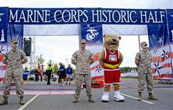 Marine volunteers from Quantico stand guard at the start/finish line with the Marine Corps Marathon's mascot, Miles, in preparation for the Historic Half in Fredericksburg on May 16.