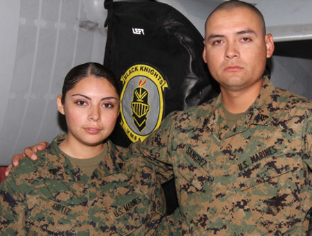"Corporals Juan Sanchez, a powerline mechanic, and Karla Ortiz, maintainance administrative clerk with Marine Fighter Attack Squadron 314, stand behind the ""Black Knights"" logo, March 3. They joined at different times but have ended up in the same squadron."