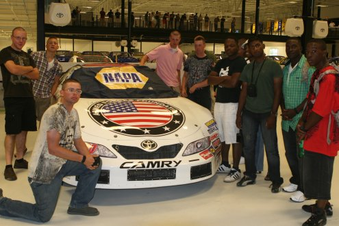 Marines from the Jacksonville area pose in front of a racecar promoting United States service members during a tour of NASCAR driver Michael Waltrip's museum, Raceworld USA, July 24, 2010.