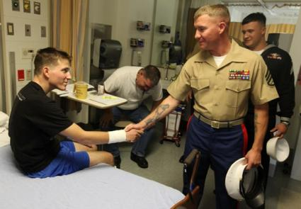 Staff Sgt. Amos Good, right, a platoon sergeant with 2nd Battalion, 7th Marines, aka 2/7, greets Lance Cpl. Aaron McNally, a rifleman with 2nd Battalion, 6th Marines, aka 2/6, at the Veterans Affairs Hospital here Oct. 7, 2010. Amos and nine other service members with 2/7 and USS Makin Island visited wounded Marines at the hospital as a way to bring Fleet Week San Francisco to service members who couldn't make the trip. McNally, a Clear Field, Utah, native, sustained injuries from an improvised explosive device while deployed with 2/6 in Afghanistan.