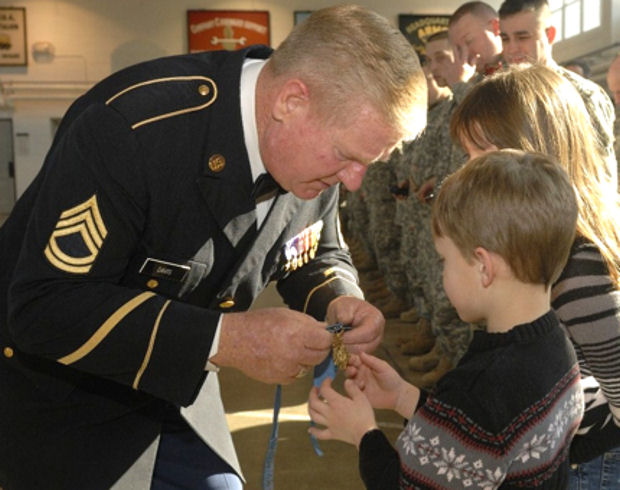 Medal of Honor Recipient Sammy L. Davis shows his Medal of Honor to 6-year-old Dean Campbell during a visit with soldiers and family members from the Indiana National Guard's 2219th Brigade Support Company at the National Guard Armory in Bedford, Ind., Feb. 13, 2010.