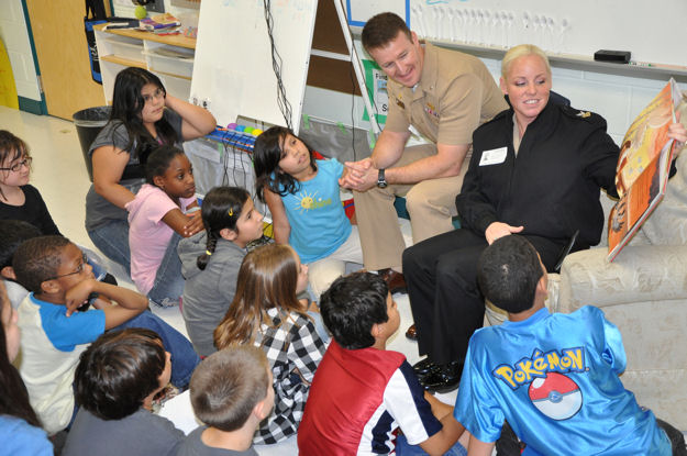 Cmdr. Mark Hofmann, left, commanding officer of Navy Operational Support Center, San Antonio, and Yeoman 1st Class Dana Gilbert, read a story to children at Carl Wanke Elementary School during San Antonio Navy Week on April 16, 2010.