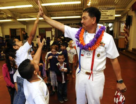 Pearl City, Hawaii (Dec. 13, 2010) Commander Navy Region Hawaii (CNRH) Command Master Chief Marc Sibal gives high-fives to Pearl City Elementary students. CNRH is partnered with Pearl City Elementary as part of a School Partnership Program, a community outreach initiative where Navy commands work with local public schools. (U.S. Navy photo by Mass Communication Specialist 2nd Class Mark Logico)