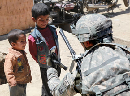 Vermont Army National Guard Capt. Stephen Iaquinto from Berlin, N.J., and a member of the 86th Infantry Brigade Combat Team, shows Afghan children a picture from his camera in Bagram, Afghanistan, May 24, 2010.