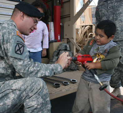 Four-year-old Jacob uses an impact wrench to help Pfc. Gary Wright from Brigade Support Battalion, 5th Brigade, 1st Armored Division, remove a bolt, May 1, 2010 at the Sierra Providence Health Network Children's Hospital in El Paso, Texas.