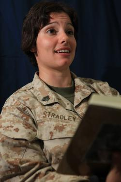 Sgt. Nikole Stradley, a radio operator with Service Company, Combat Logistics Battalion 26, 26th Marine Expeditionary Unit, and mother of a 9-month-old reads a book while being videotaped for the United Through Reading Program, Sept. 23, 2010.