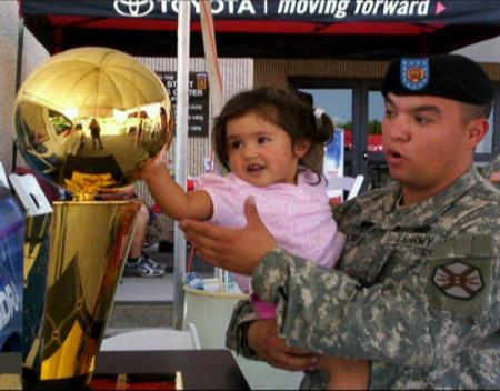U.S. Army Staff Sgt. Gabriel Villalobos, a military intelligence analyst with Intelligence and Sustainment Company, Headquarters and Headquarters Battalion, 101st Airborne Division, holds his then 4-year-old daughter, Briana, while they check out an NBA trophy at Fort Bliss, Texas, in the summer of 2008. Villalobos is a U.S. citizen who grew up in a Mexican border town. He joined the U.S. Army to give back to the country that has given him so much.