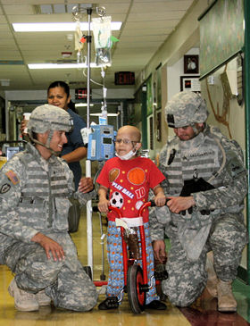 Sgt. Willie Lebeouf, left, and Sgt. Cesar Castellanos from 5th Brigade, 1st Armored Division, pose with 6-year-old Aaron at the Sierra Providence Health Network Children's Hospital in El Paso, Texas, May 1, 2010.