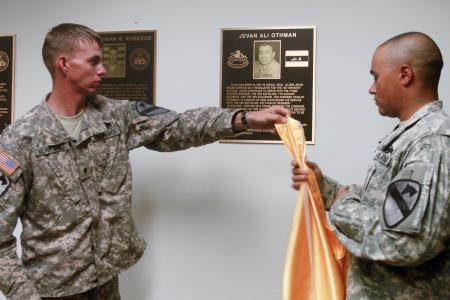 Spc. James Heaward (left), and Spc. Evan Arnold, both with Headquarters and Headquarters Company, 3rd Battalion, 8th Cavalry Regiment, 3rd Brigade Combat Team, 1st Cavalry Division, unveil the dedication plaque of Jevan Ali Othman, an interpreter that was killed in February, 2009 by a vehicle-borne improvised explosive device while serving the battalion in Mosul, Iraq. The battalion's headquarters building and Headquarters and Headquarters Company conference room were dedicated, Aug. 11, 2010 in honor of the individuals killed in the blast.