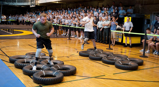 Marine Corps Lance Cpl. Joshua Wege and Army Pvt. Harrison Ruzicka race past a cheering Corps of Cadets crowd as they make their way through the indoor obstacle course test at Arvin Gymnasium at the U.S. Military Academy, West Point, N.Y., Sept. 10, 2010. U.S. Army photo by John Pellino