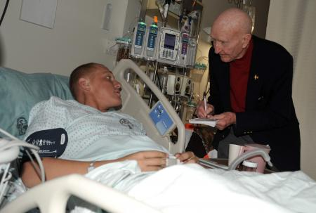 "Col. Gail Halvorsen, a retired Air Force colonel known as the Berlin Airlift ""Candy Bomber,"" talks to a U.S. Marine, Lance Cpl. Drake Bies, at Landstuhl Regional Medical Center in Germany. Halvorsen recorded contact information for loved ones of the warriors whom he met at the hospital. The airlift icon is touring Europe and Southwest Asia this week to encourage servicemembers and learn about the evolution of his heritage."