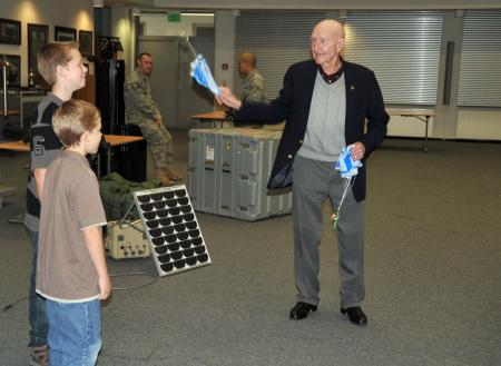 Retired Col. Gail Halvorsen helps two children test their parachutes with toy soldiers holding candy bars. The soldiers were part of decorations created by the 435th Contingency Response Group at Ramstein Air Base, Germany. After briefing him on their mission, the group surprised the WWII veteran with a cake celebrating his 90th birthday. The Berlin Airlift veteran is known for his role in strengthening U.S.-German ties after a goodwill gesture of air dropping candy bars to children in East Berlin turned into a full-scale operation that ended in more than 20 tons of candy delivered via small parachutes. He is touring Europe and Southwest Asia this week to visit and encourage service members.
