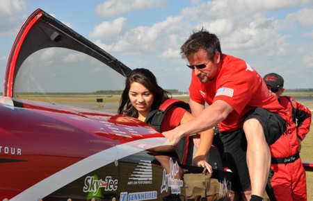 Dax Wanless, a pilot with Greg Poe Airshows, helps Nicole Goetz, 17, prepare for her flight in the ethanol-powered Fagen MXS with Greg Poe March 23, 2011. Nicole was recently selected as the United States Air Force Military Child of the Year and was awarded a flight in air show performer Greg Poe's aerobatic airplane.